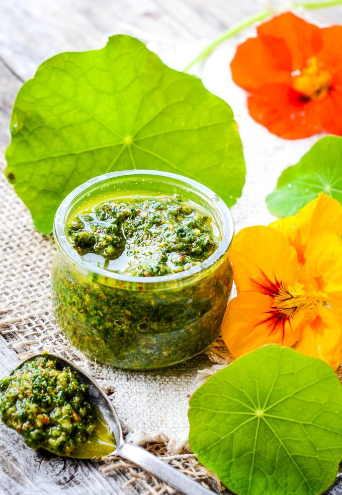 jar of pesto with flowers and leaves
