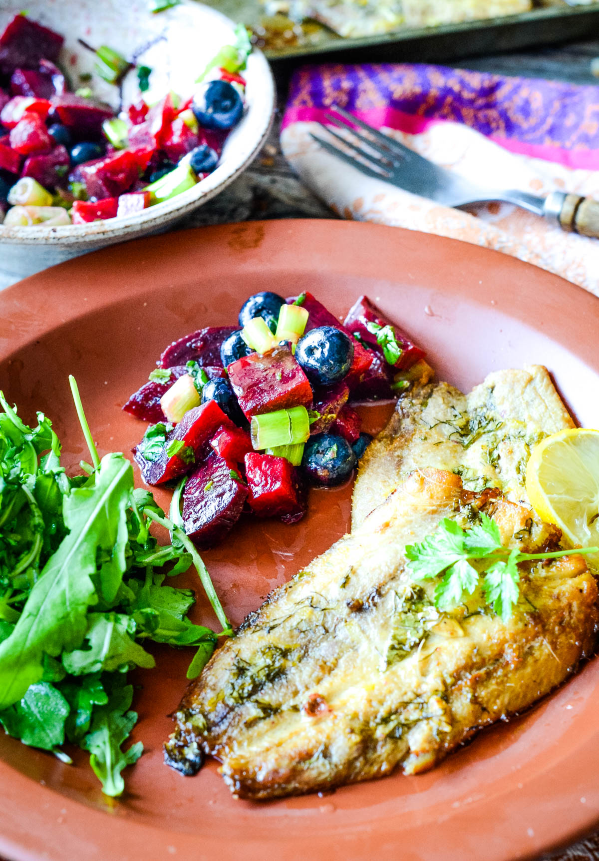 baked sardines with blueberry and beetroot salsa on plate
