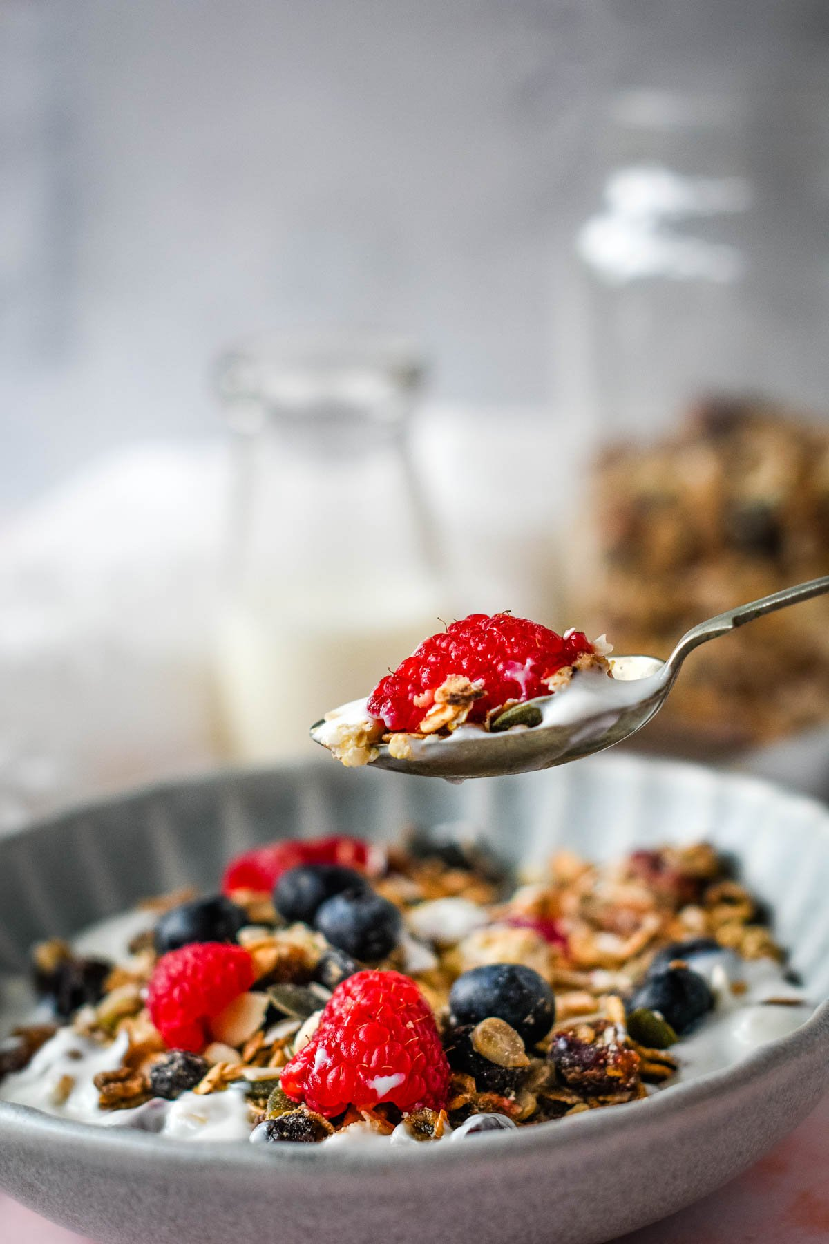 raising a spoonful of granola at breakfast table