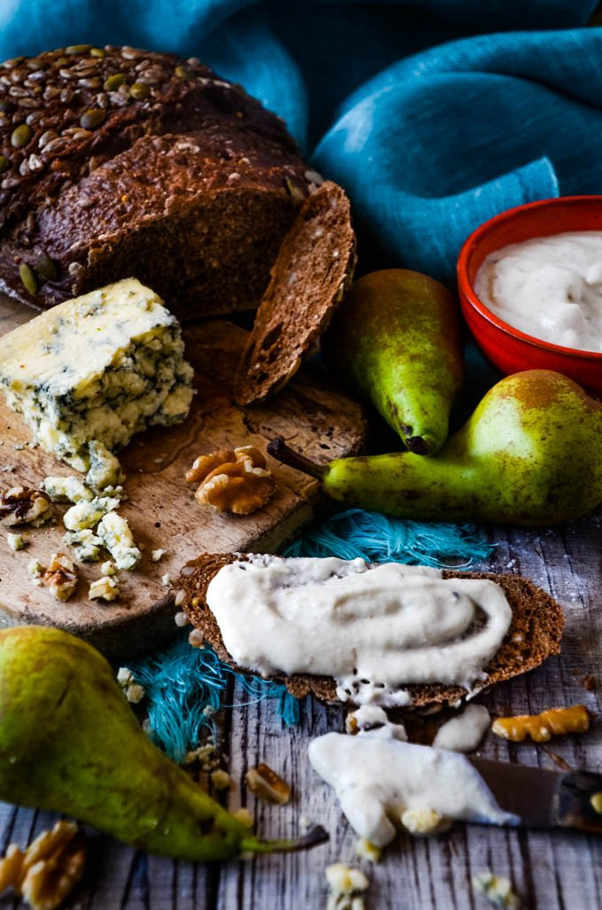 blue cheese dip spread on bread with ingredients behind