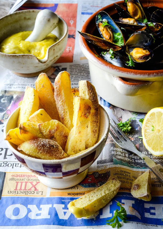 long table shot of chips in bowl and mussels behind