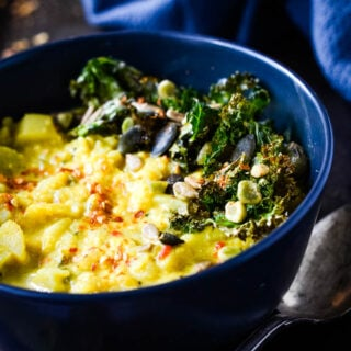 curried cauliflower soup in bowl with kale crisps