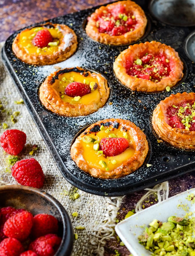 oven tray with tarts and raspberries