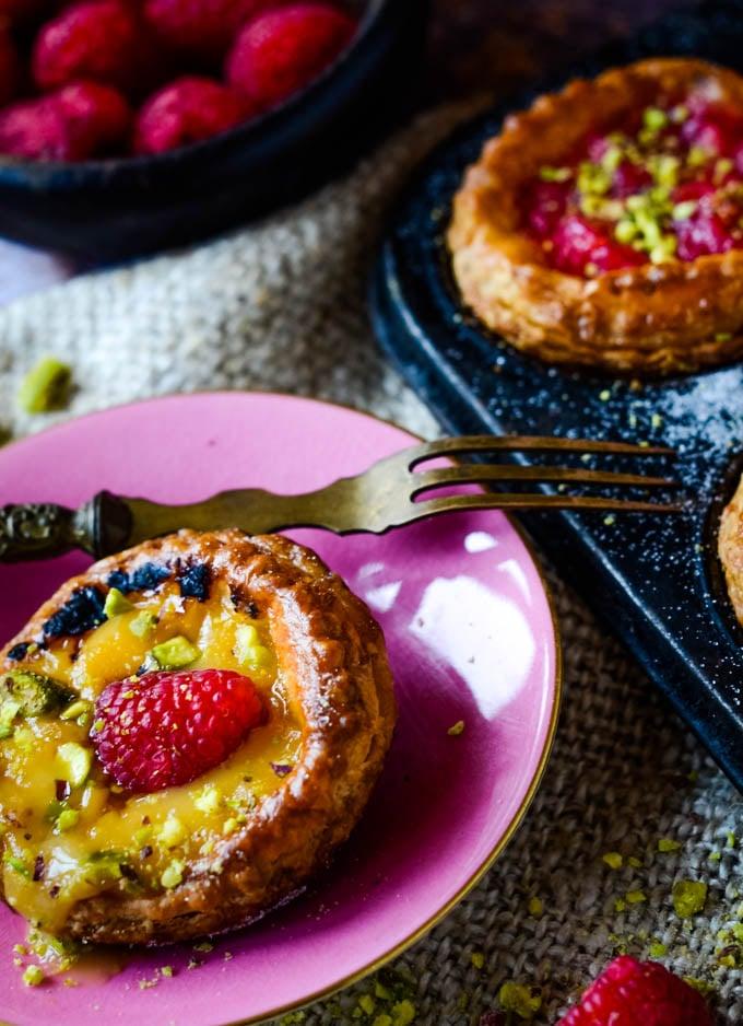 single raspberry tart on pink plate