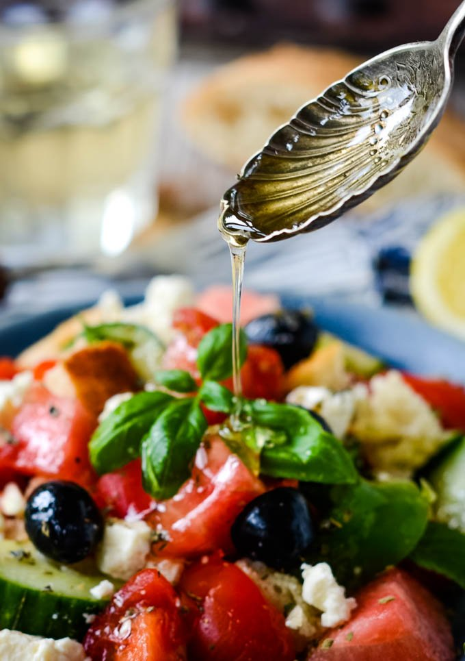 spoon drizzling honey on salad