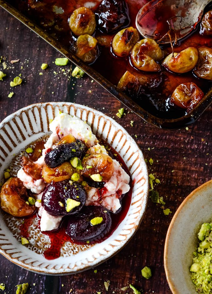 baked grapes with labneh and pistachios in small white bowl with baking tray of grapes behind