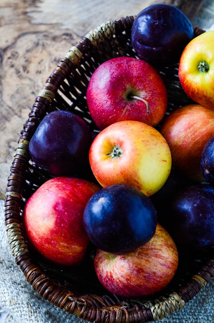 plums and apples in a basket