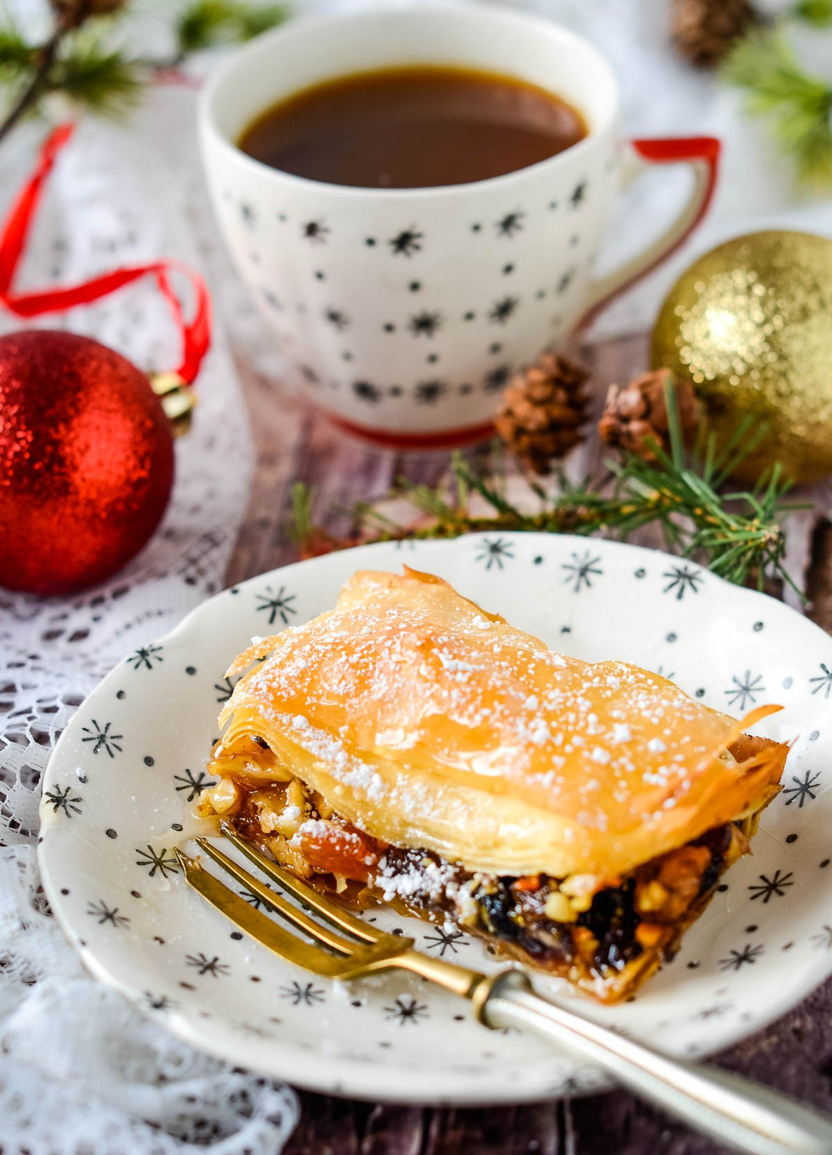 Christmas baklava on plate with cup behind