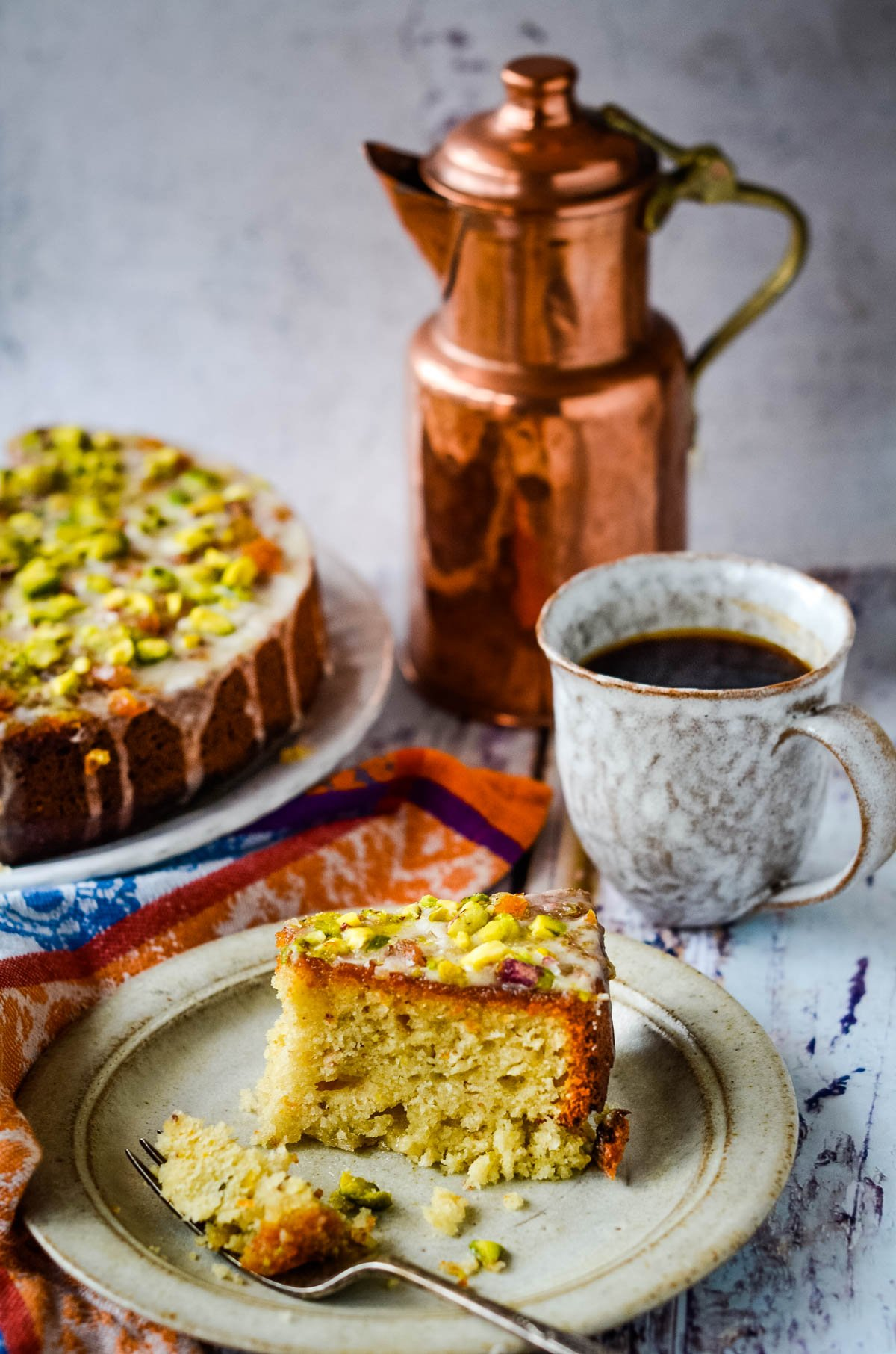 slice of cake with coffee pot behind