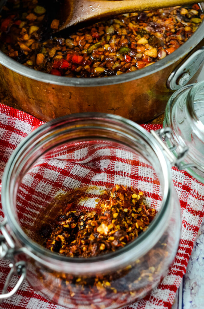 dry spice mix in jar with chilli in oil behind