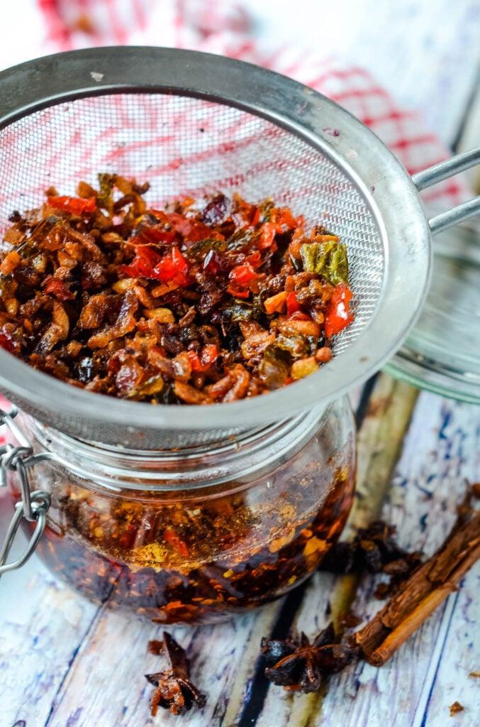 straining the chilli in oil into jar