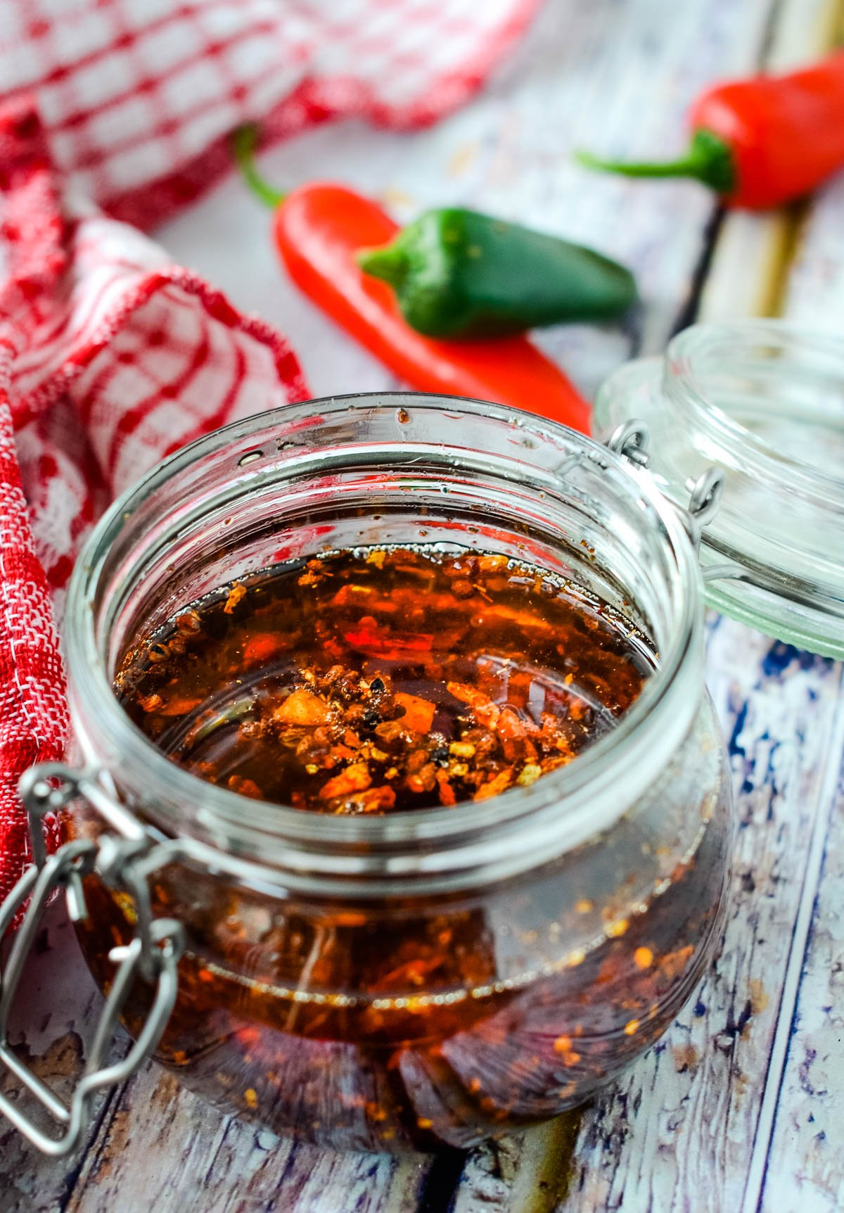 jar of crispy chilli in oil with chilli peppers behind jar