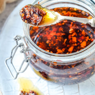 hot crispy chilli peppers in oil with spoon over jar