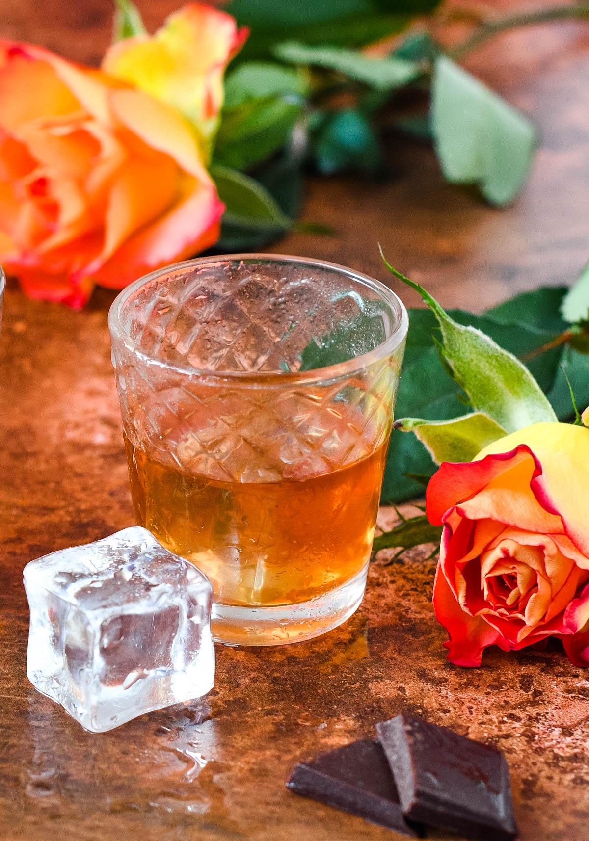 close up of glass of whisky liqueur with ice cube at the side and rose behind