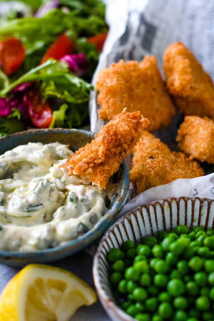 fish finger being dipped into tartare sauce