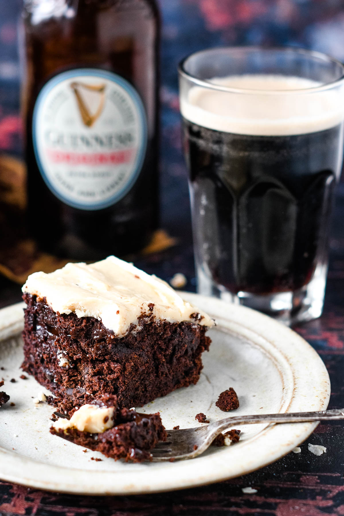 close up of brownie on plate with fork and Guinness behind