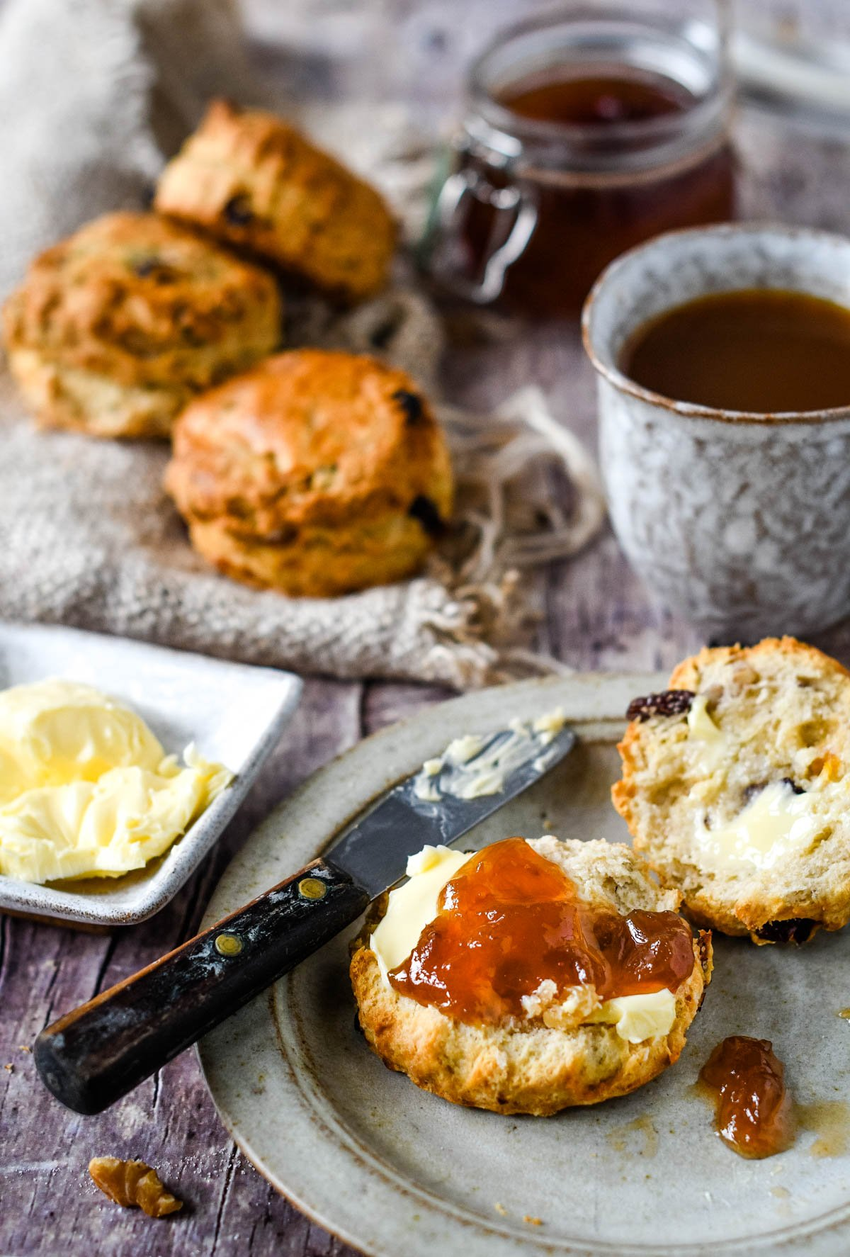 mixed fruit and nut scones on tea table with jam