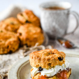 fruit scone with cream and jam and mug in background