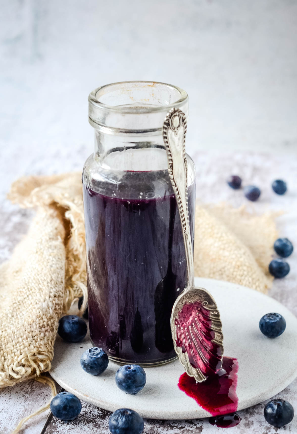 blueberry syrup in bottle with spoon at side