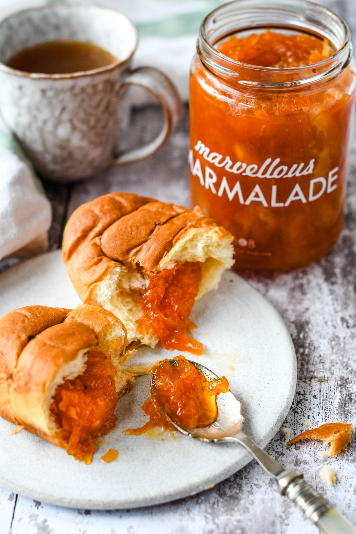 jam on crosissants with jar or marmalade behind