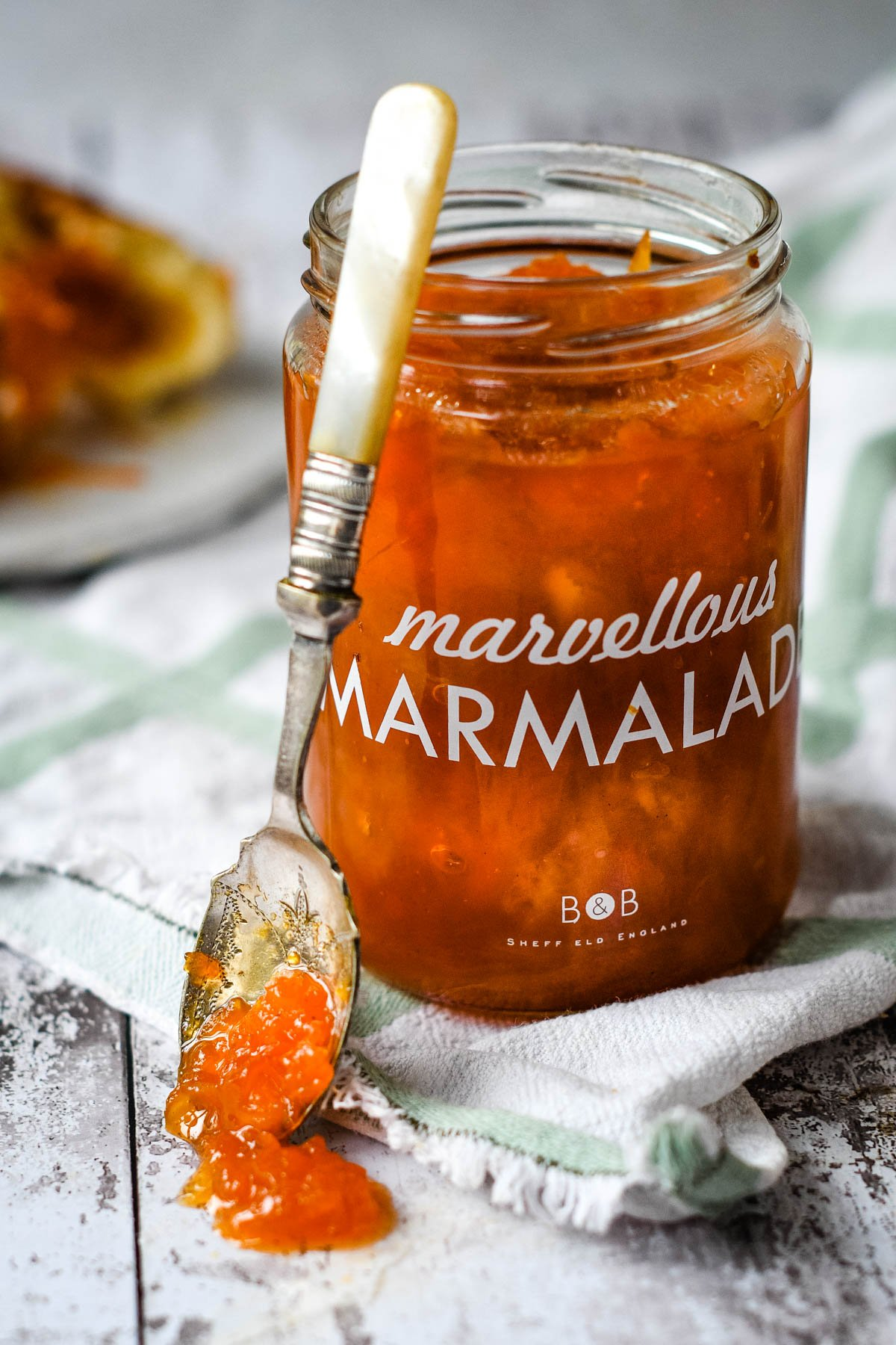 carrotr and lemon marmalade in jar with spoon at side