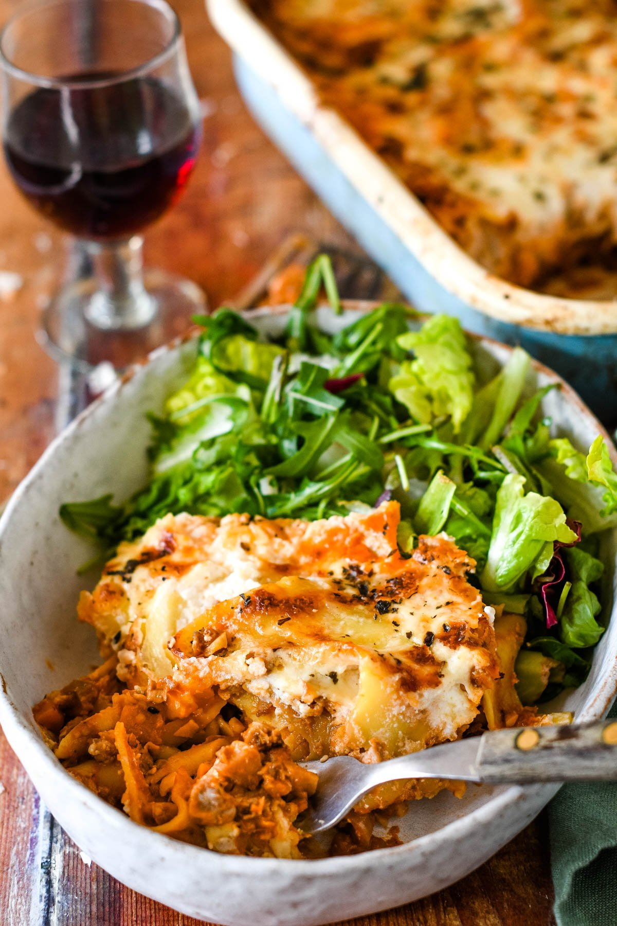 fork in bowl of lasagne