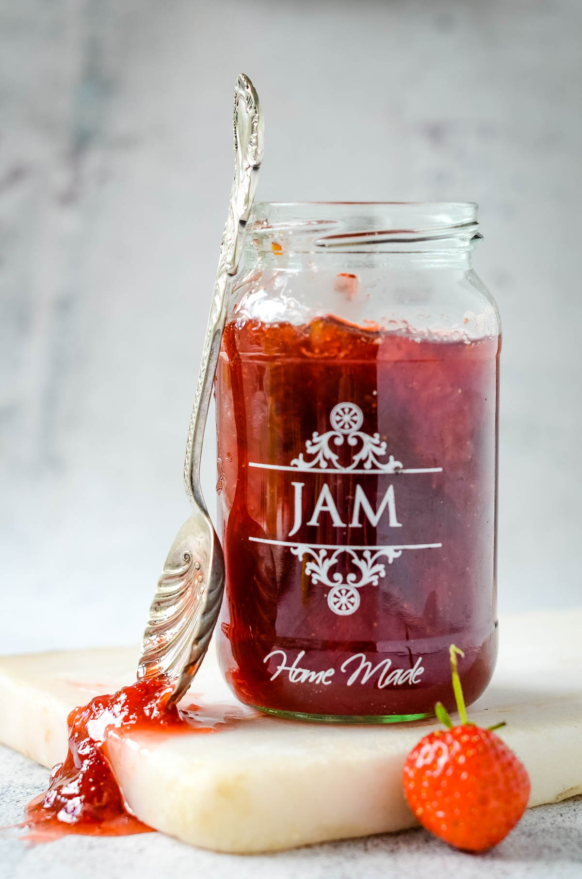 strawberry and rhubarb jam with spoon at side of jar