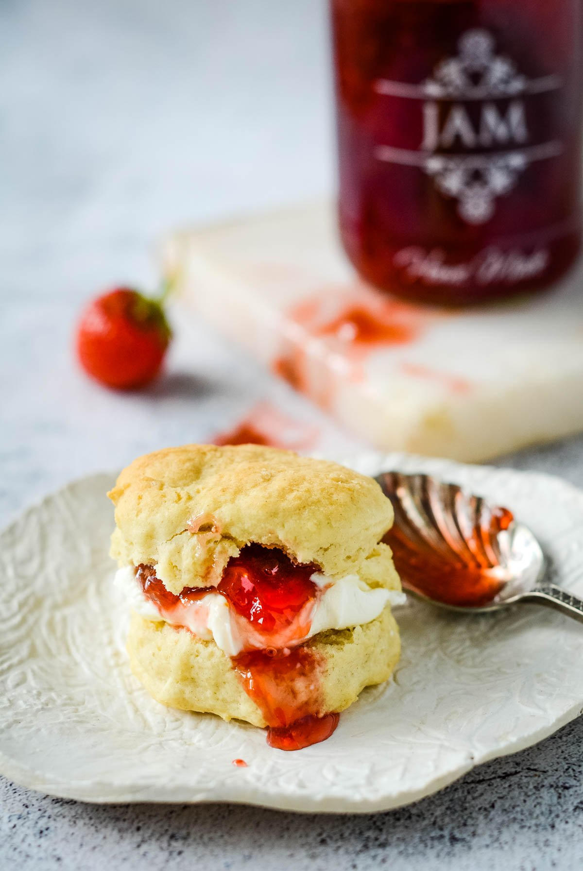 scone with jam and cream in front of jar