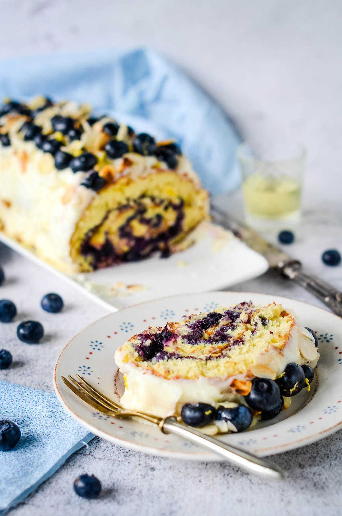 blueberry and lemon roulade with a slice cut off on plate