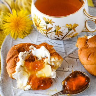 dandelion jelly on croissant with tea behind