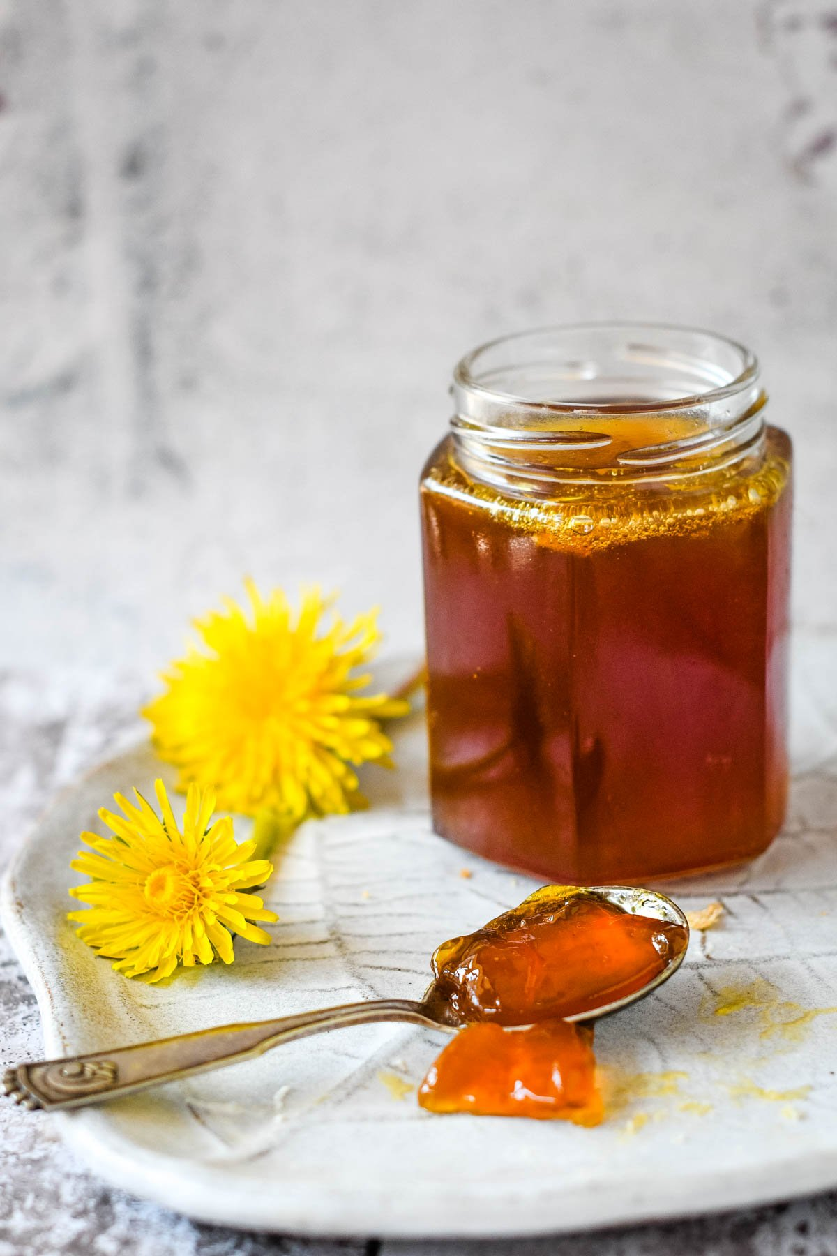 jar or dandelion jelly with spoon in front