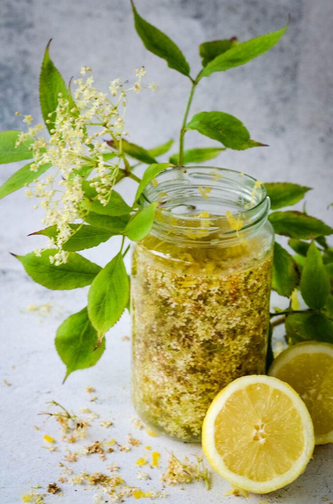 elderflowers soaking in vodka with lemon beside jar