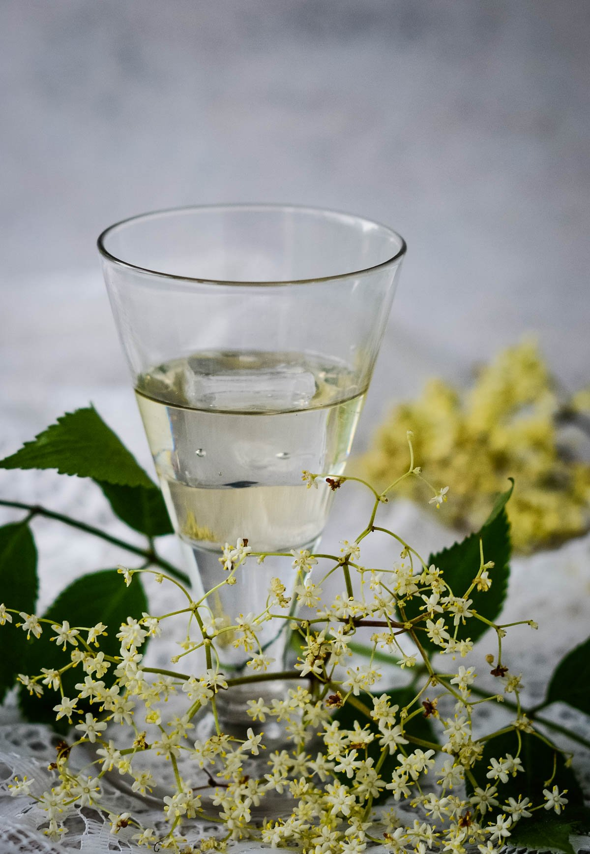 glass of liqueur with flowers behind