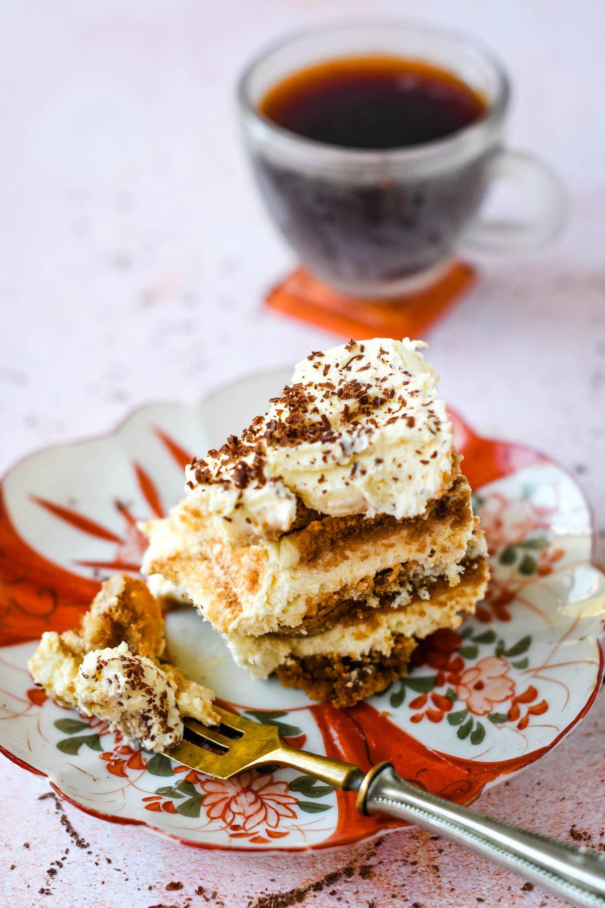 fork in slice of tiramisu with espresso coffee behind
