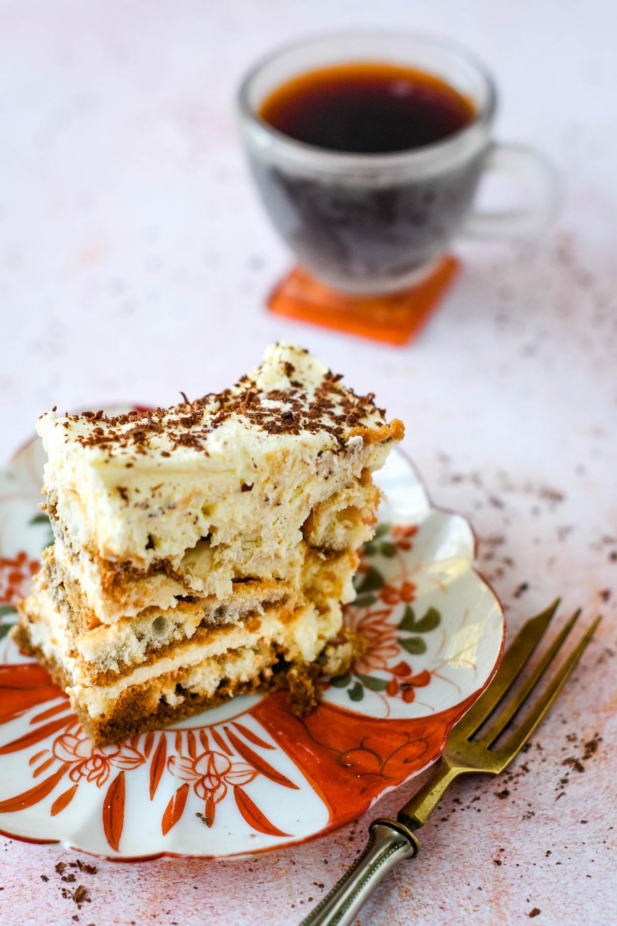 tiramisu slice with espresso coffee behind