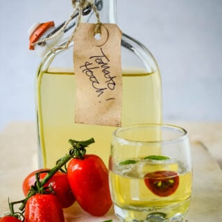 tomato water liqueur in bottle with shot glass in front and bunch of tomatoes at side