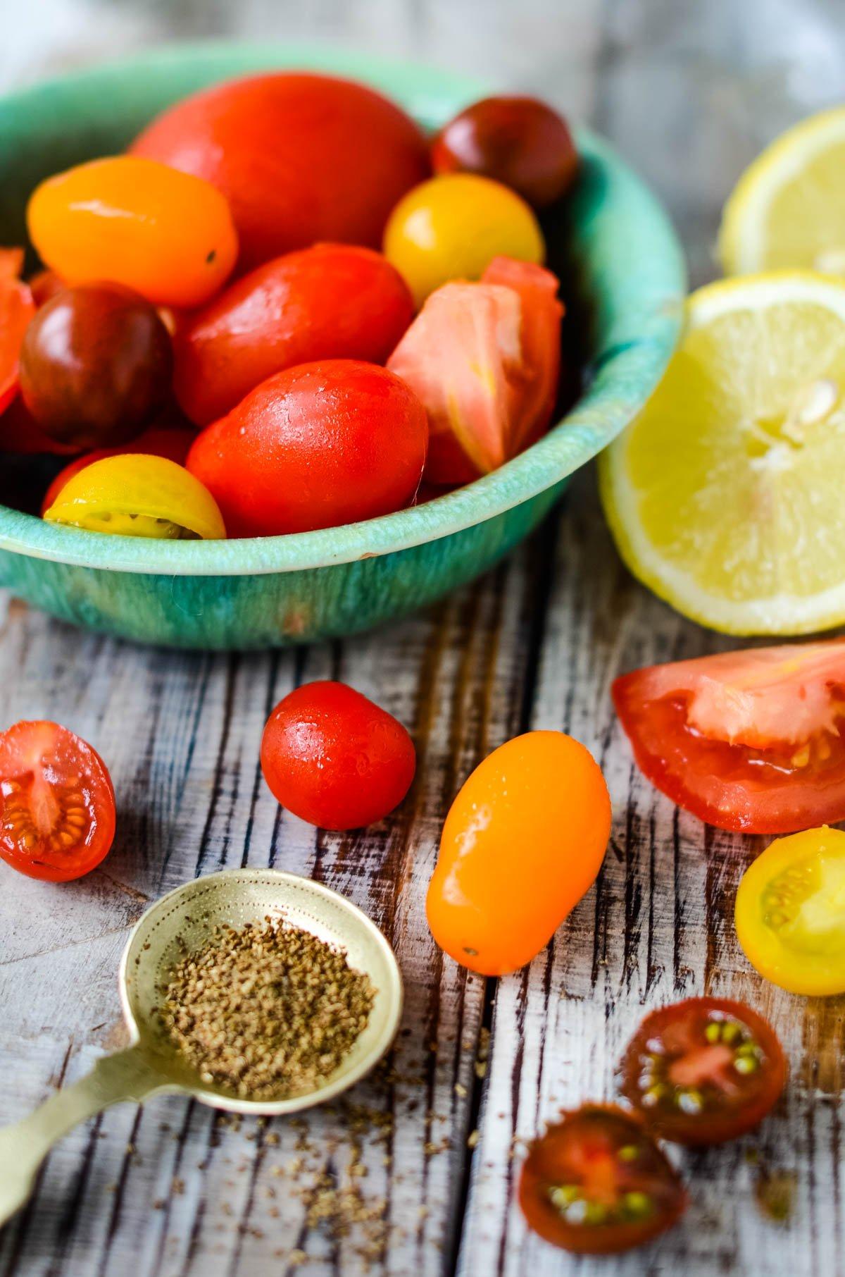 ingredients - tomatoes, lemon, salt, celery seeds on wooden board