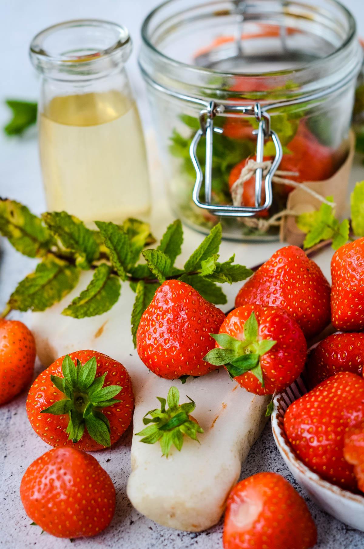 ingredients - strawberries with leaves, mint and vinegar with jar behind