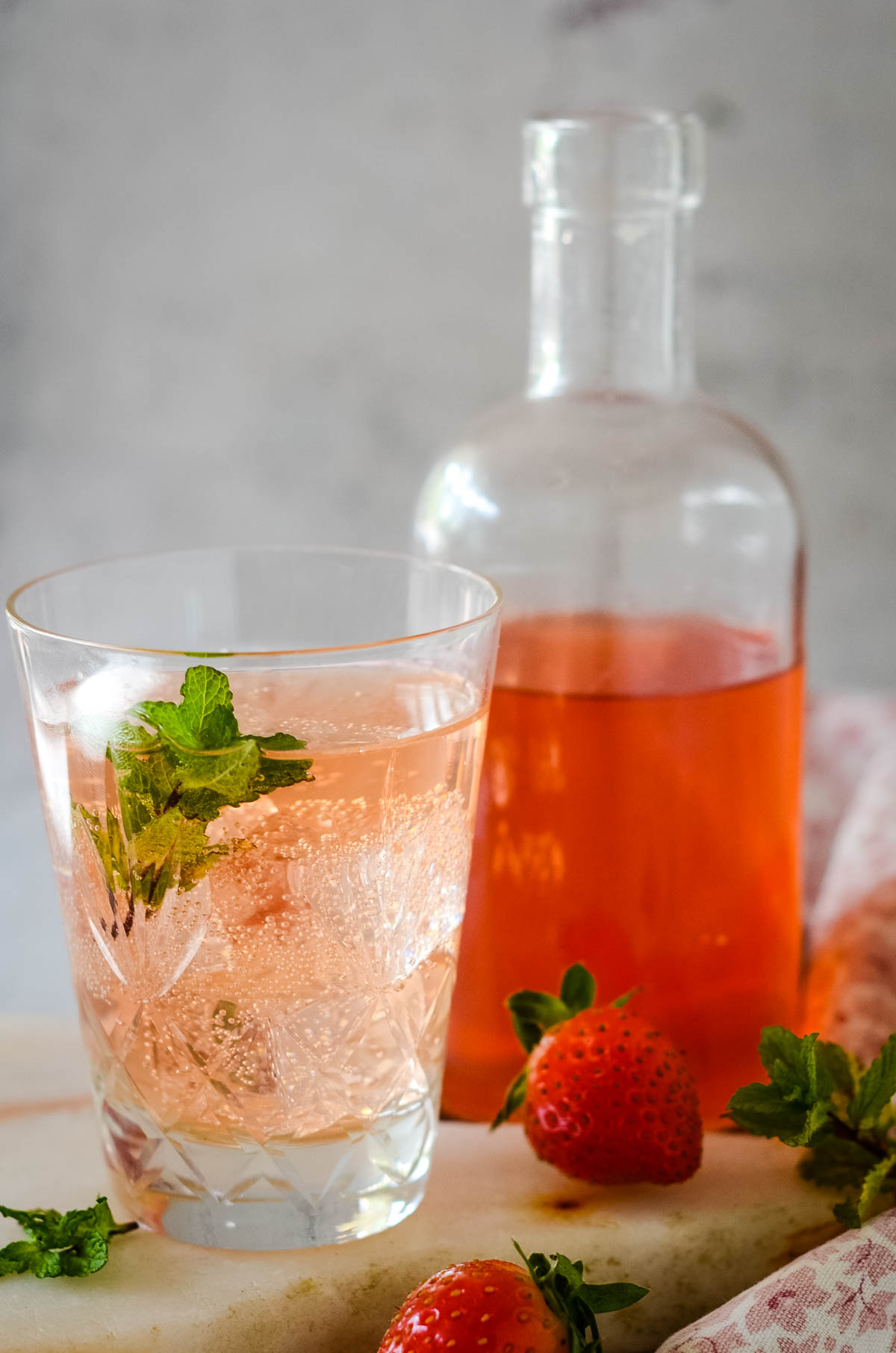bottle of cordial behind small glass with drink in it and mint leaves on top