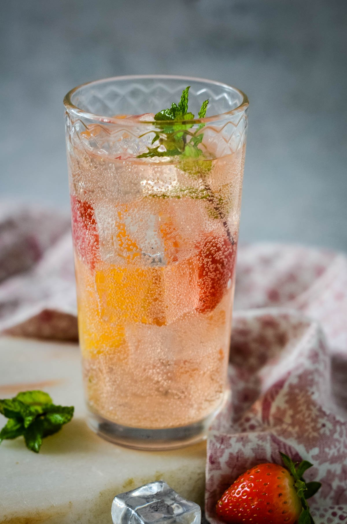 strawberry and mint shrub diluted with soad in a tall glass