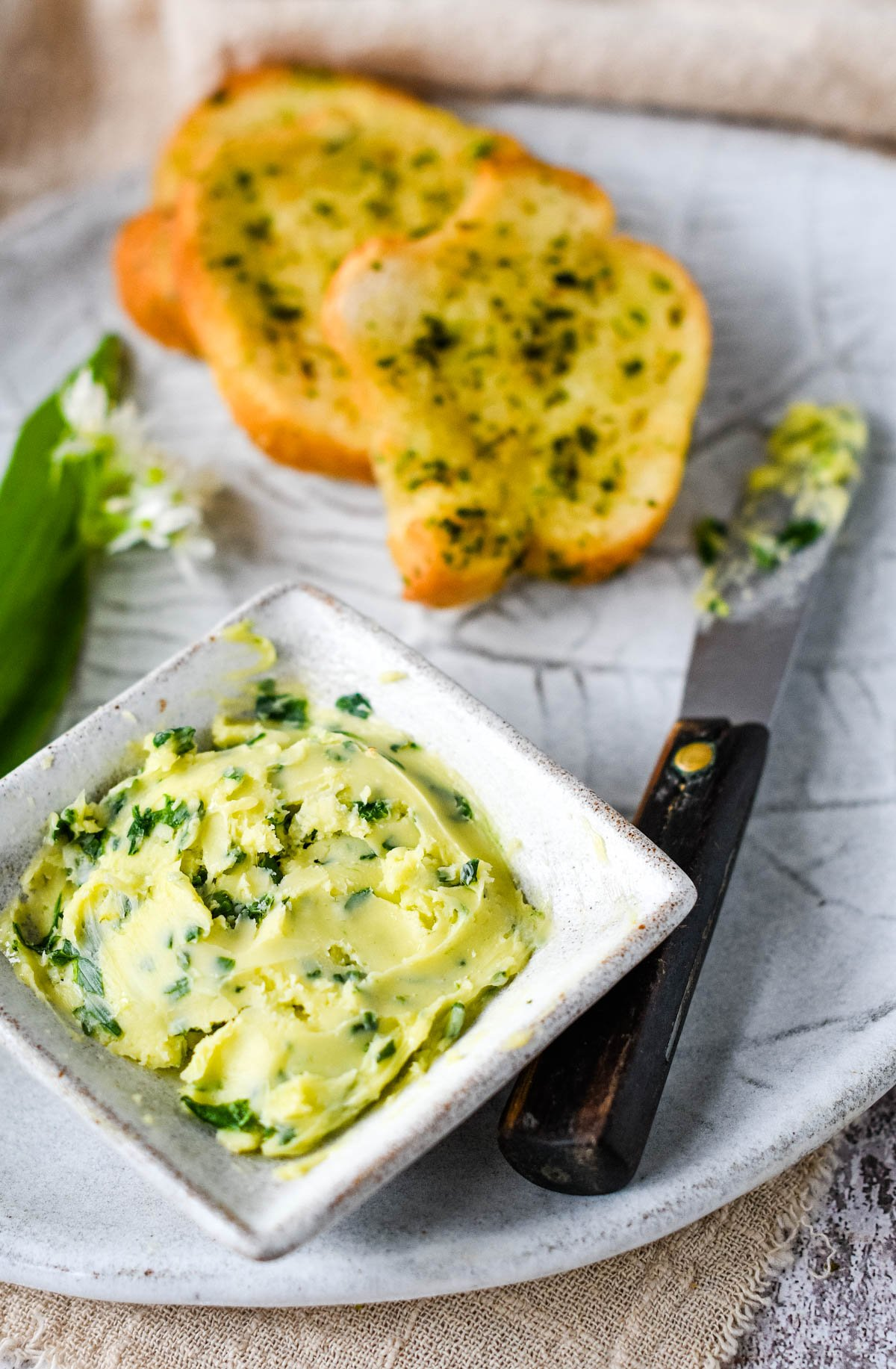 wild garlic butter in square white bowl with slices of garlic bread behind
