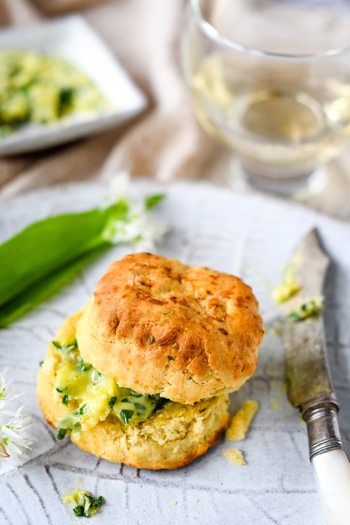 butter on a scone with wild garlic leaves and flowers at the side