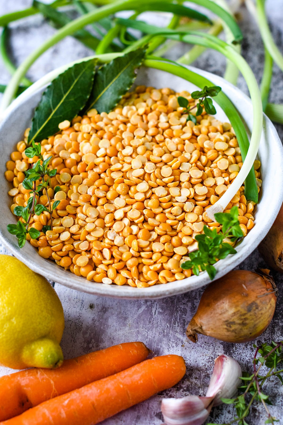 ingredients - yellow split peas, bay leaves, thyme, olilve oil, carrots, onions, garlic, lemon and spring onions
