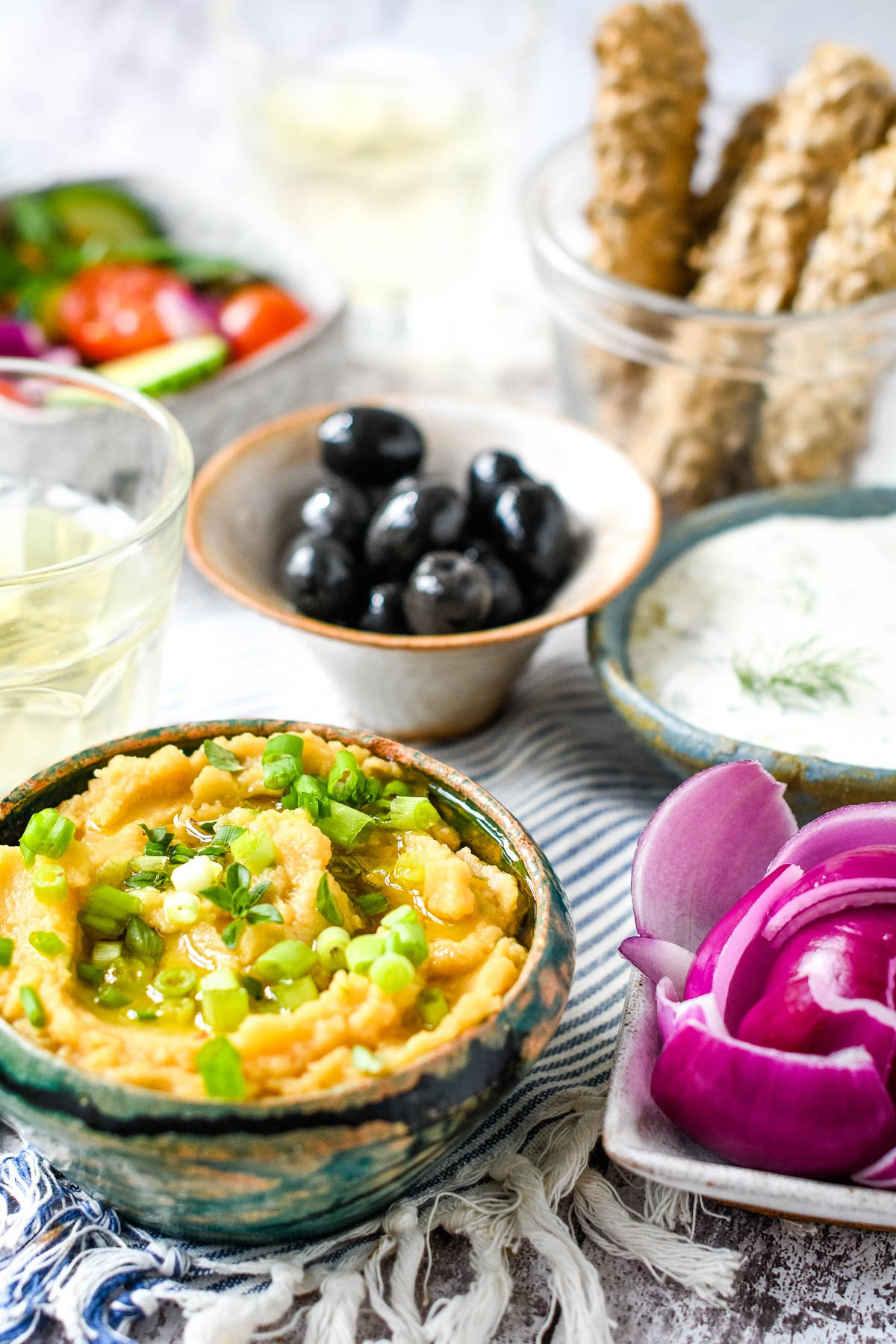 Greek fava dip with other dips, bread sticks and wine on table