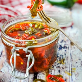 candied chilli peppers in jar with pickle fork