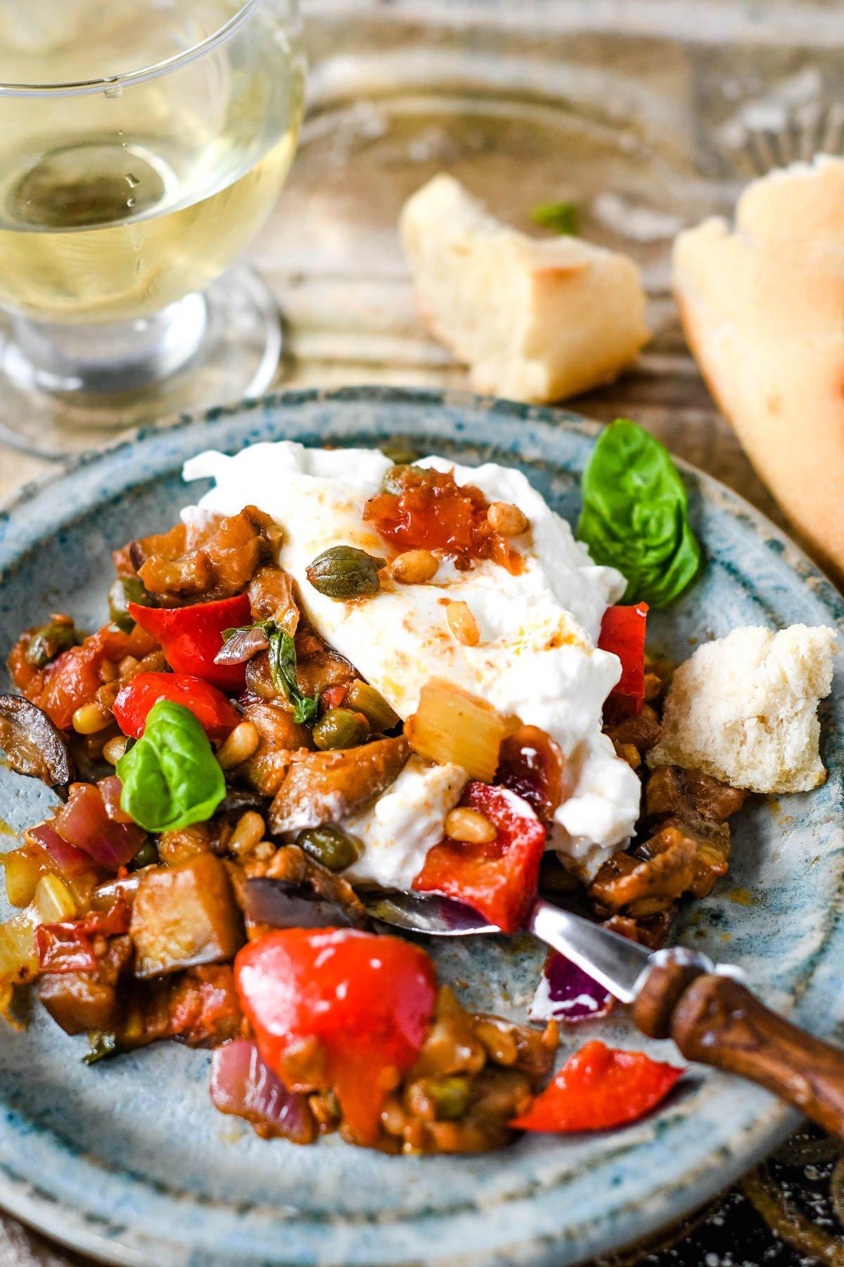 caponata in dish with fork and mozzarella cheese