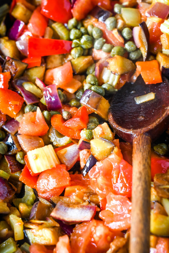adding the aubergines, tomatoes and capers to other veg in pan