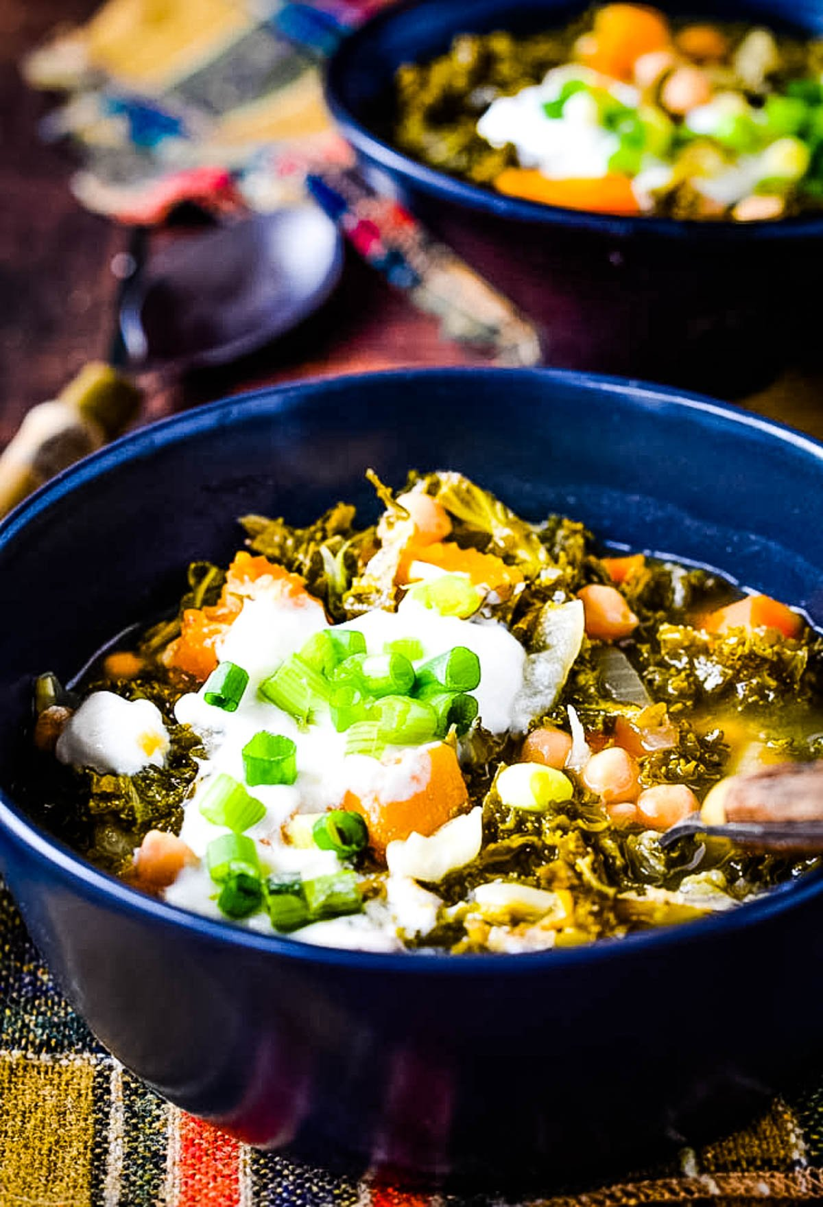 squash kale and chickpea soup in black bowl with another boal behind